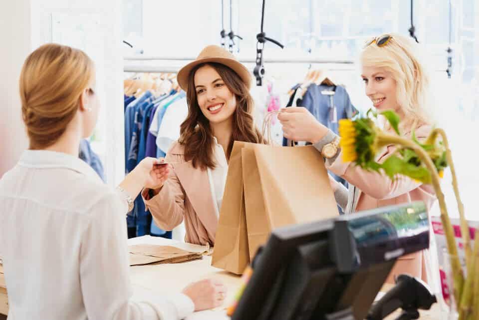 click en collect of bopus - twee dames die bestelling komen afhalen bij winkelmeisje in de winkel