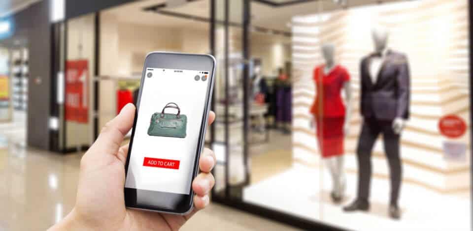 hand met smartphone met webshop solden bij kledingzaak