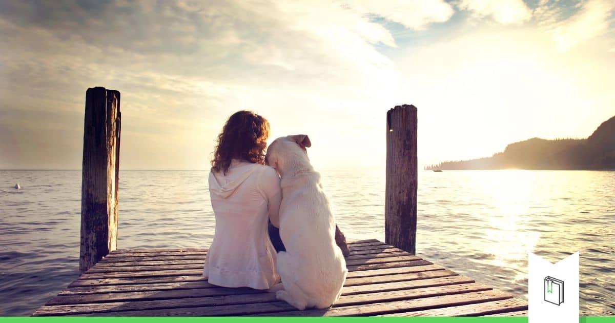 vrouw en hond kijken samen naar zonsondergang