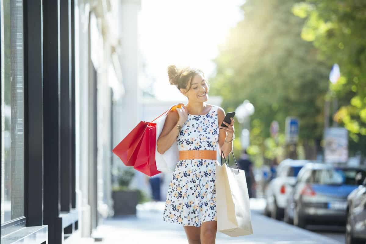jongedame kijkt op haar telefoon tijdens het shoppen